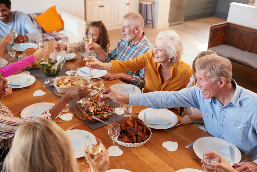 Multi-Generation Family Making A Toast With Wine As They Meet For Meal At Home